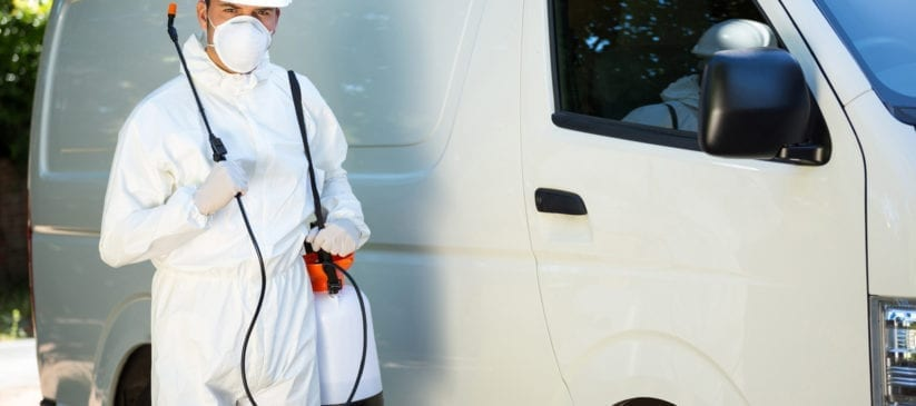 Pest control man standing by white van, with sprayer in hand